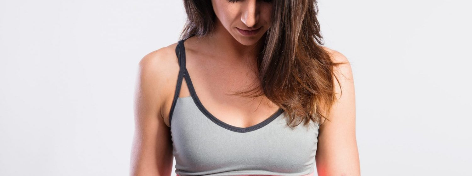 Attractive young fitness woman in gray tank top. Studio shot on gray background.